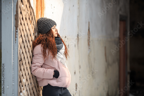 A young cute white girl in a hat warm scarf and gloves is standing in the corridor of a ruined house in winter. Destroyed building.