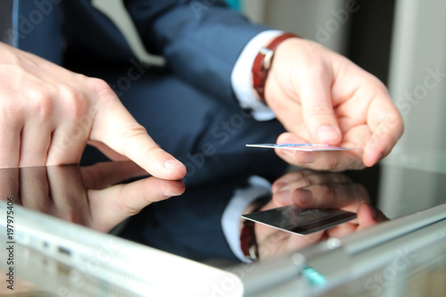 business man entering data of a credit card . On-line shopping on the internet using a tablet