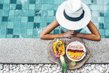 Girl eating exotic fruits in the pool