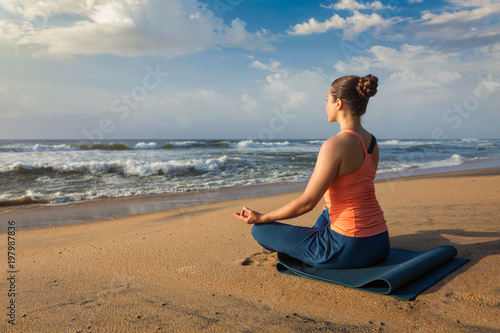 Foto op Aluminium School de yoga Woman doing yoga Lotus pose oudoors at beach
