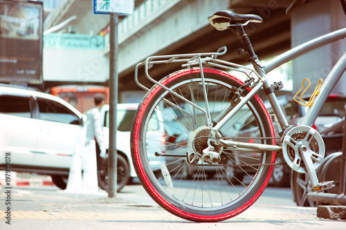 Foto op Plexiglas Fiets Bicycle at parking space with background traffic steet in the city at