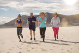Senior people and sports coach running on sandy beach