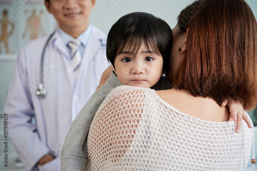Back view of young woman holding her cute little son on hands while discussing treatment with highly professional pediatrician, toddler looking at camera with deep black eyes