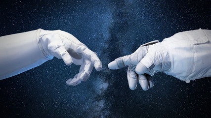 two near touching hands in space suits, 'God touches Adam' pose