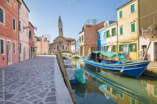 In de dag Venetie Typical canal with colorful facades with vibrant colors and Church of San Martino and its leaning campanile in famous fishermen village on the island of Burano, Venice, Italy