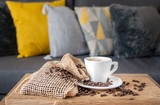 A cup of espresso coffee and a saucer with freshly roasted coffee beans on a rustic table. Decorative pillows on a gray sofa in the background.