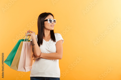 Portrait of a smiling young asian girl holding shopping bags
