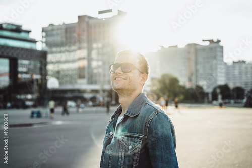 Smiling young man in sunglasses on city street