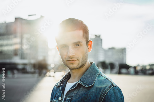 Confident young man in jeans jacket on city street