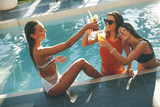 Young women drinking coctail and having fun by swimming pool - 198051697