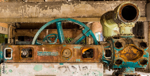 Fotobehang Oude verlaten gebouwen Old, colorful industrial machines at an abandoned power plant. Large turquoise colored wheels and rusty equipment.