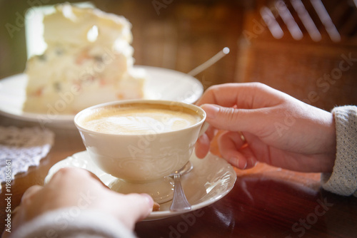 woman's hand holding cappuccino cup in the cafe
