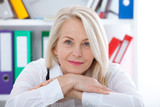 Lovely middle-aged blond woman with a beaming smile sitting at office looking at the camera - 198083063