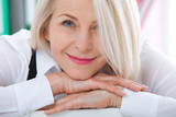 Lovely middle-aged blond woman with a beaming smile sitting at office looking at the camera - 198083074