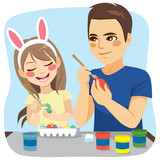 Happy family of father and daughter painting easter eggs