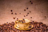 Cup with roasted flying coffee beans