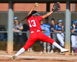 Girl winding up and throwing a fastball for a strike during a softball game