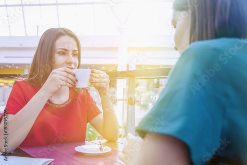 Two pretty happy joyful woman best friend having fun with cups  of coffee (Friendship, communication concept)