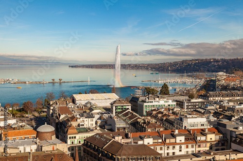 Fotobehang Bleke violet Geneva water jet fountain with rainbow. Geneva aerial view from St. Pierre Cathedral bell tower. Winter day in Geneva, Switzerland.