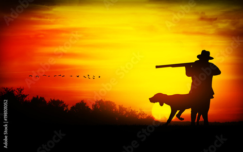 Fotobehang Geel hunter with dog at sunset