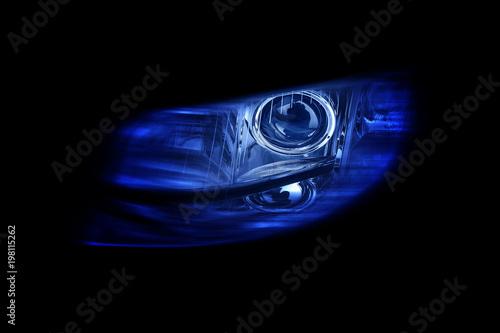 Nowożytny automobilowy reflektor na czarnym tle błyszczy niebieskiego światło.