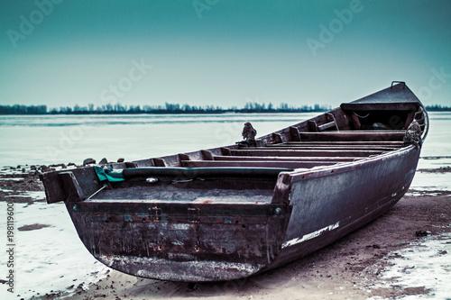 Fotobehang Schipbreuk Old rusty boat thrown ashore on a winter morning