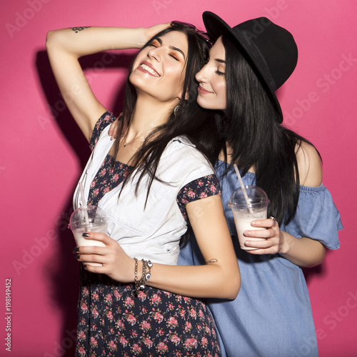 Two caucasian brunette hipster woman in casual stylish outfit having fun drinking milkshakes with straws. They standing on a bright pink background. Cheerful, happy emotions - 198149452