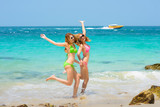 both women are enjoy and happy together on the sea beach in summer time with blue sky and cleared water in background