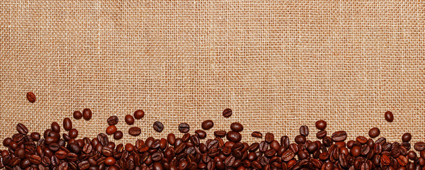 Panorama lined with coffee beans on the background of sack cloth © blackguitar1