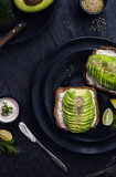 Wholegrain Toast with avocado and creamy cheese,fresh lemon and sesame on dark plate. Top view with close-up. - 198158835