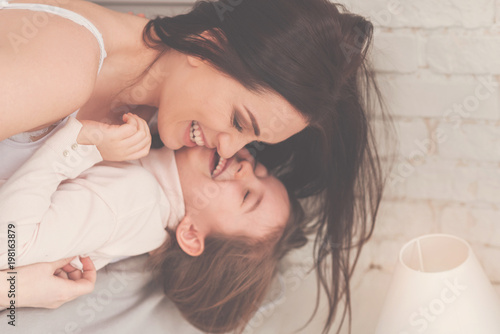 Come here, little rascal. Amazing beautiful active lady making her child laugh while goofing around and staying in bed