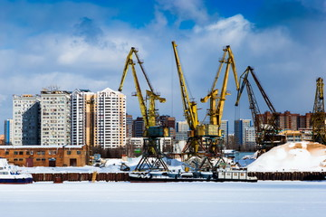 Port cranes in river port at winter day in Moscow, Russia.