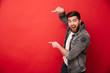 Photo of agitated man wih beard in casual clothing pointing fingers on copyspace text or product with surprise and smile, isolated over red background