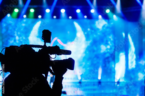 Professional Video camera operator working with his equipment, blue background - 198177886