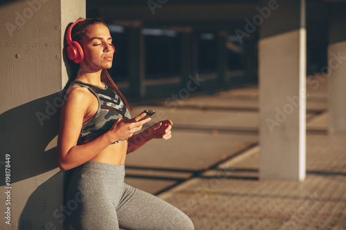 Poster Young woman resting and listen to music after jogging