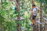 Teenager having fun on high ropes course, adventure, park, climbing trees in a forest in summer - 198178803