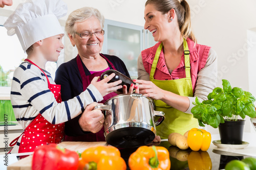 Granny, mum and son talking happily while cooking in kitchen