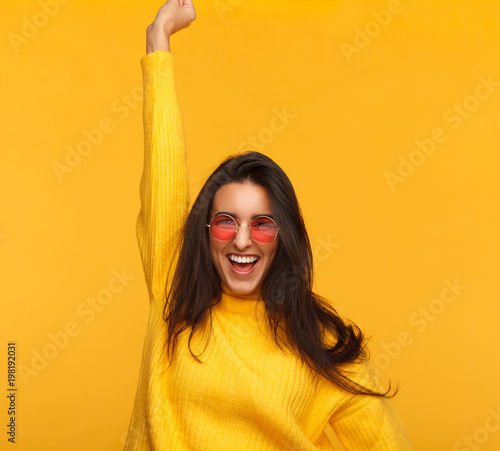 Cheerful hipster girl on yellow