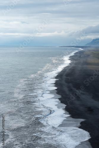 Küstenlinie mit Brandungswellen und dunklem Strand