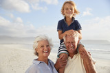Grandparents Carrying Grandson On Shoulders On Walk Along Beach