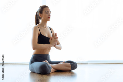 Fototapeta Beautiful sporty young woman doing yoga in lotus position at home.