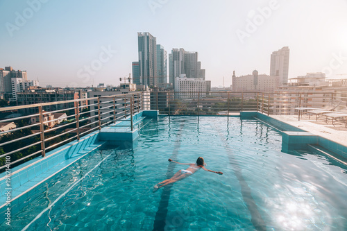 Fotobehang Bangkok Woman swimming in roof pool