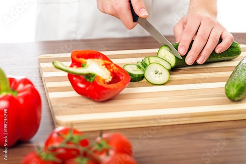Poster Chef woman cutting cucumber