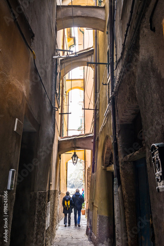 Poster Smal steegje Two senior tourists couple walking down a narrow dark alley in an Italian medieval traditional town