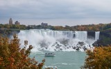 Beautiful and impressive panorama of the Niagara Falls in Ontario (Canada) on a bright autumn day with water crashing down the falls onto rocks creating lots of mist in front of the city skyline