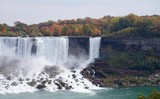Beautiful and impressive panorama of the Niagara Falls in Ontario (Canada) on a bright colorful (red, orange, yellow) autumn day with water crashing down the falls onto rocks creating lots of mist