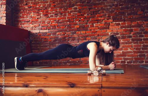 Młoda mięśniowa kobieta robi sedno ćwiczeniu na sprawności fizycznej macie w gym.