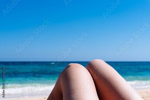 Deurstickers Canarische Eilanden Mature woman legs sunbathing on the beach