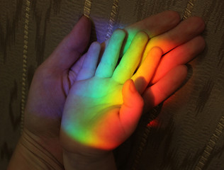 family hands and rainbow