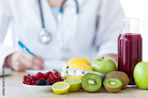 Some fruits such as apples, kiwis, lemons and berries on nutritionist table.